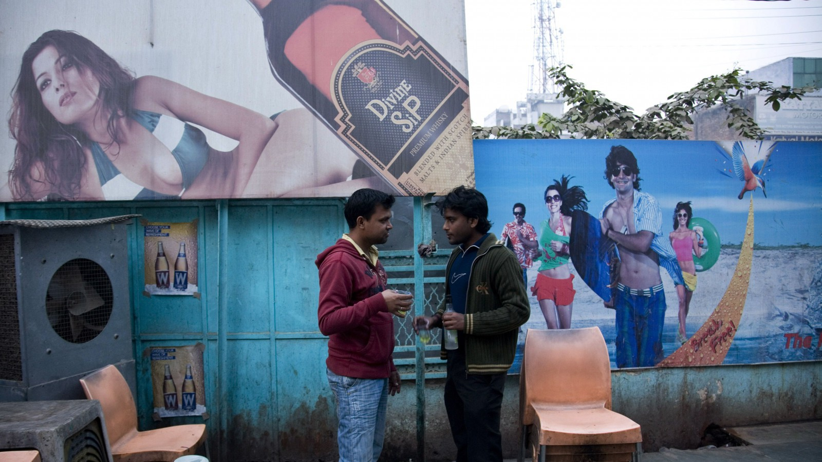 Two Indian men share a moment as they drink outside a state-sanctioned liquor shop in Allahabad, India, Thursday, Dec. 15, 2011. Despite religious and cultural taboos against drinking among Indians, 5 percent, roughly 60 million people, are alcoholics. Two-thirds of the alcohol consumed in the country is illegal hooch made in remote villages or undocumented liquor smuggled in, according to The Lancet medical journal. (AP Photo/Rajesh Kumar Singh)