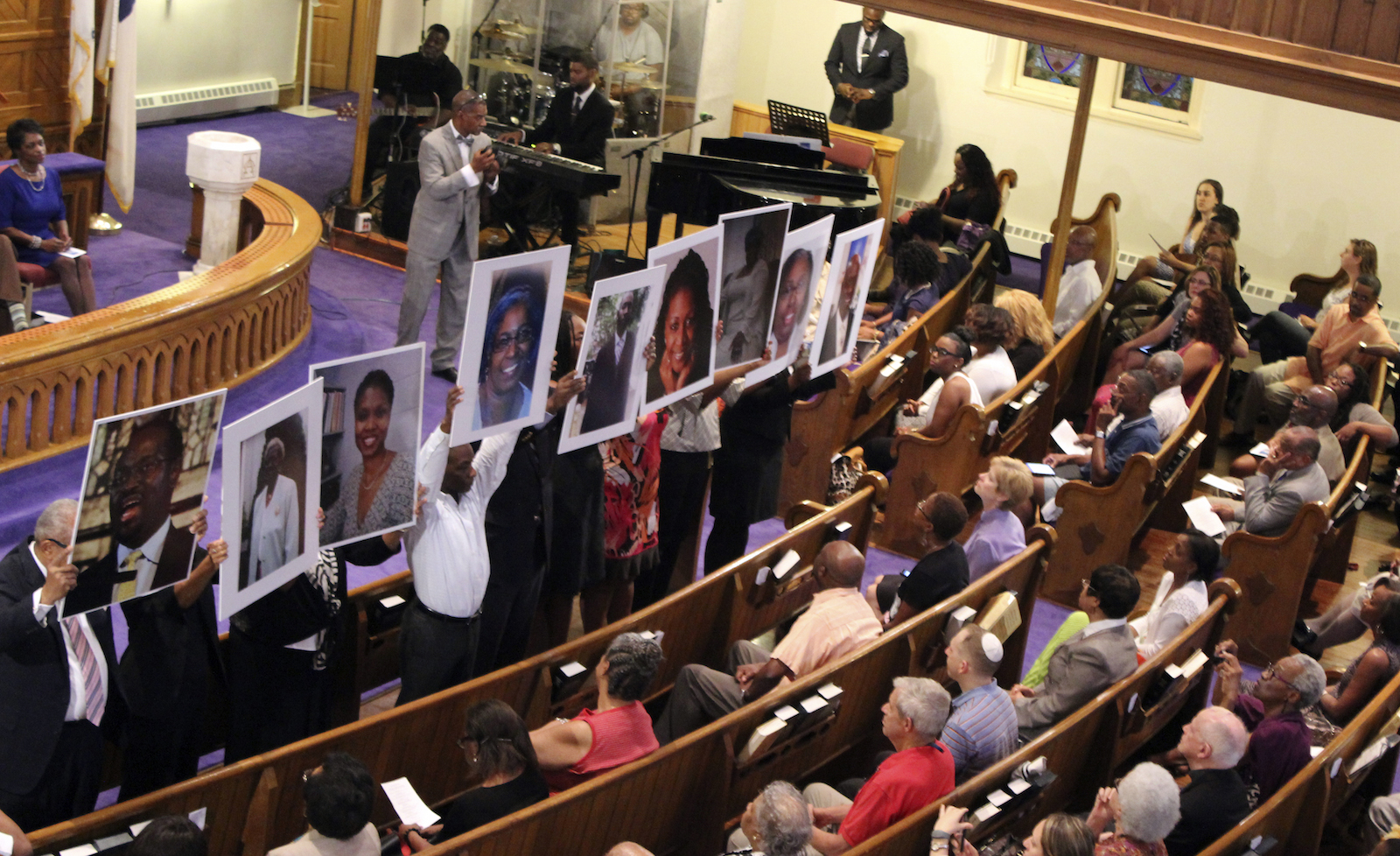 In this photo taken June 19, 2015, photos of the victims of the shooting at Emanuel AME Church in Charleston, S.C., are held during a vigil at the Metropolitan African Methodist Episcopal Church in Washington. The black church has long been the cornerstone and sanctuary for African American life. It has also long been a target for racists and white supremacists trying to strike blows against the African American psyche. The latest attack came Wednesday in Charleston, South Carolina, when 21-year-old Dylann Storm Roof joined a prayer meeting inside historic Emanuel African Methodist Episcopal Church and shot nine people dead, including the pastor, the Rev. Clementa Pinckney, and other ministers.