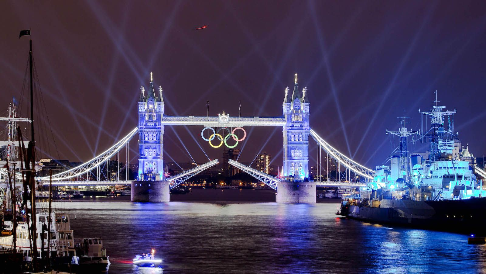 The speedboat, bottom left, carrying the Olympic Flame, heads to Tower Bridge during the Opening Ceremony at the 2012 Summer Olympics, Friday, July 27, 2012, in London.