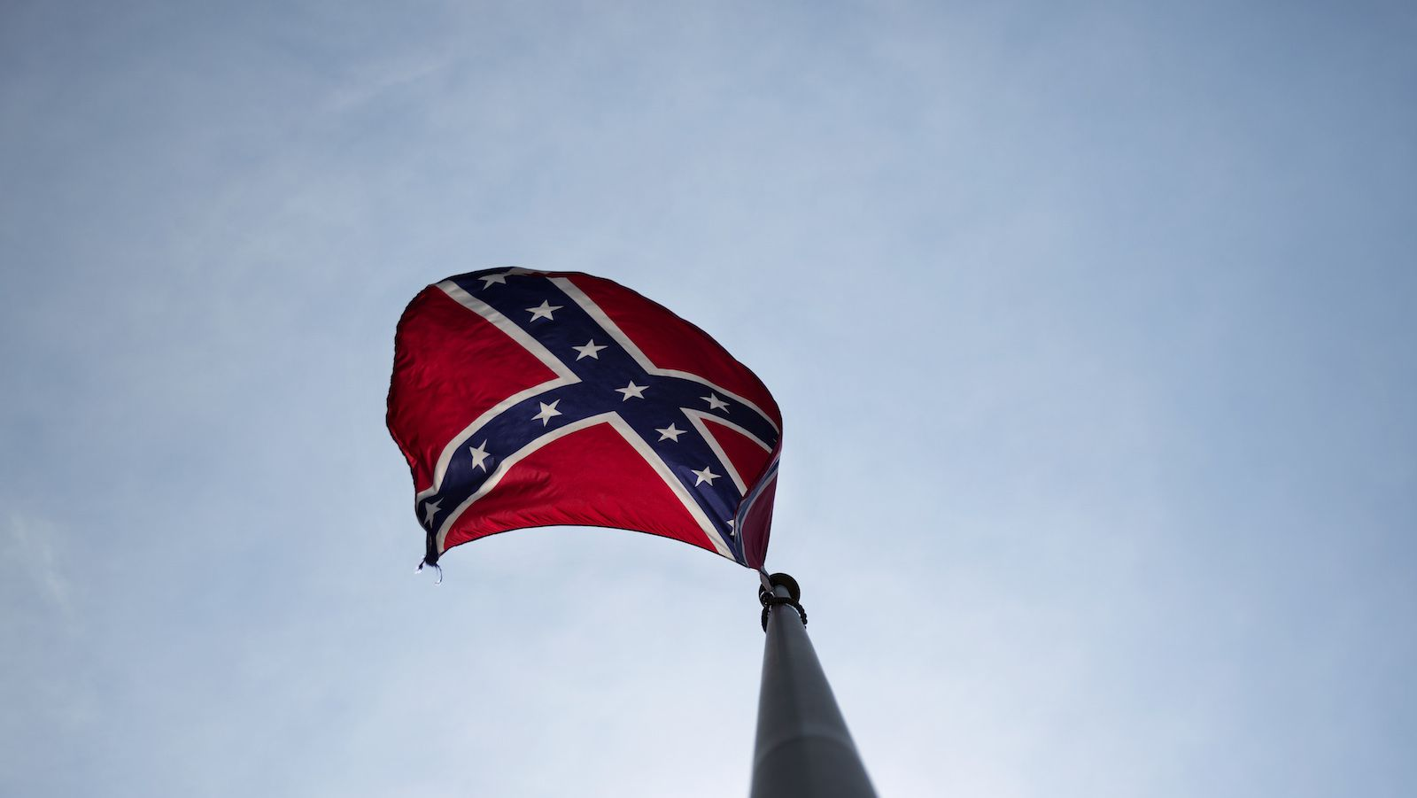 "A Confederate flag flies at the base of Stone Mountain Tuesday, June 30, 2015, in Stone Mountain, Ga. At Georgia's iconic Stone Mountain - where the Confederacy is enshrined in a giant bas-relief sculpture, the Ku Klux Klan once held notorious cross-burnings and rebel battle flags still wave prominently, officials are considering what to do about those flags. The park, which now offers family-friendly fireworks and laser light shows, is readying its ""Fantastic Fourth Celebration"" Thursday through Sunday, and multiple Confederate flag varieties are still displayed at the mountain's base."