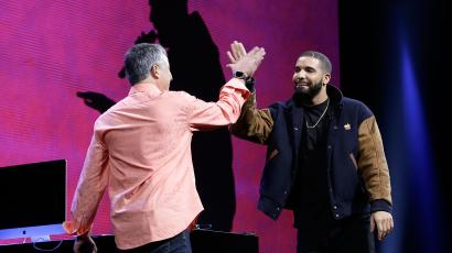 Musician Drake, right, high fives Eddy Cue, Apple senior vice president of Internet Software and Services, during the Apple Worldwide Developers Conference in San Francisco, Monday, June 8, 2015.