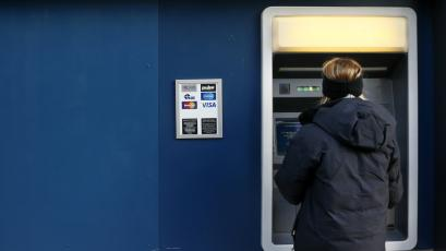 a woman uses an ATM machine in downtown Pittsburgh, Pennsylvania.