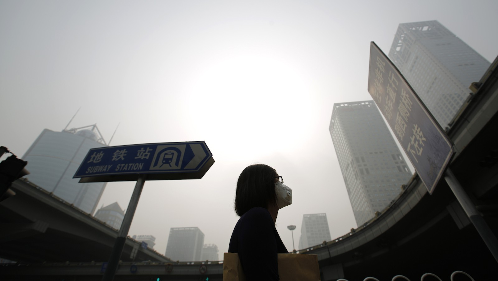 A woman wearing a mask makes her way on a street amid heavy haze and smog in Beijing