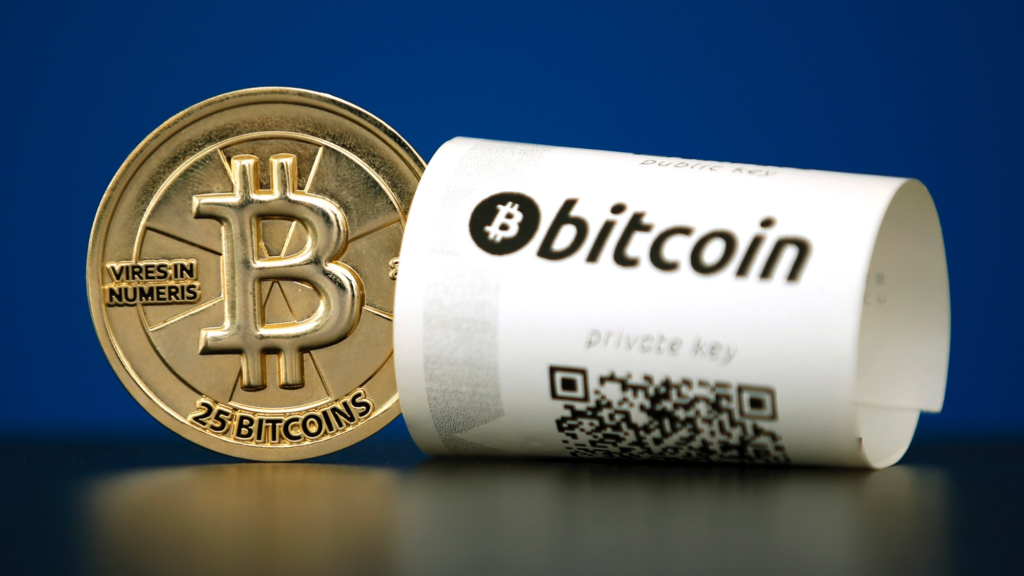 """A Bitcoin (virtual currency) paper wallet with QR codes and a coin are seen in an illustration picture taken at La Maison du Bitcoin in Paris, France, May 27, 2015. British authorities have come out in support of digital currencies in the name of promoting financial innovation, while proposing that regulations should be drawn up to prevent their use in crime. But it is technophiles who are leading the drive to make London a real-world hub for trade in web-based """"cryptocurrencies"""", of which bitcoin is the original and still most popular.   Picture taken May 27, 2015.  REUTERS/Benoit Tessier - RTX1EWTP"""