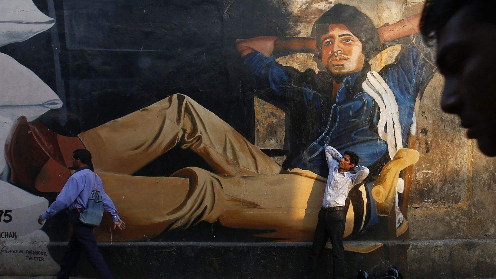 "Ram Pratap Verma, a 32-year-old aspiring Bollywood film actor, poses in front of a mural of actor Amitabh Bachchan in Mumbai May 1, 2013. Bollywood is an addiction for many; an addiction that attracts thousands of aspiring stars to the city of Mumbai. Ram Pratap Verma made the journey from his small village eight years ago, and despite carrying his whole ""home"" inside his bag, he is determined not to give up on his ambitions. He endeavours to watch at least one film a week at a cinema, where the silver screen keeps his dreams alive. Picture taken May 1, 2013."