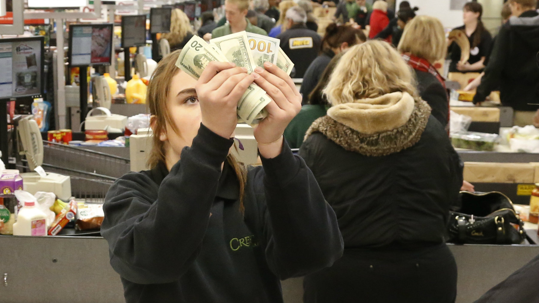 Cashier Nikki Hall checks the cash given to her at the register in the check out line at a crowded Crest Fresh Market grocery store in Edmond, Okla, Wednesday, Dec. 4, 2013. A winter storm expected to plow through Oklahoma starting Thursday. (AP Photo/Sue Ogrocki)