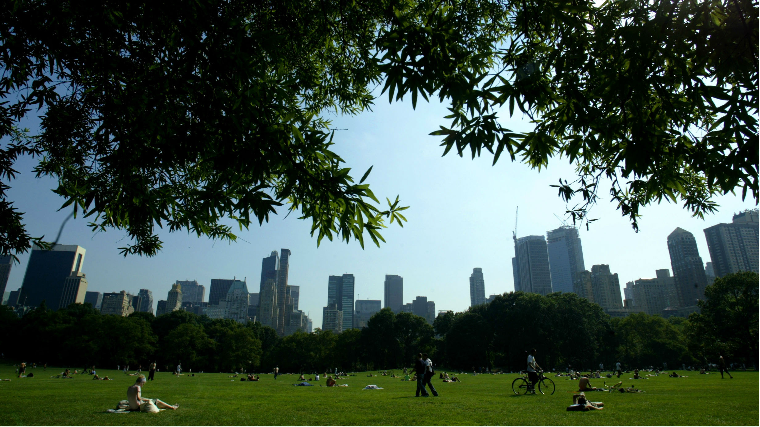"""Park goers relax on the Sheep's Meadow in New York's famed Central Park, July 15, 2003. Central Park, arguably America's most famous public green space, turns 150 years old this summer. For New Yorkers, the park, in the middle of Manhattan is an urban oasis. It's 843 acres, with some 26,000 trees, 58 miles of pathways, 9,000 benches, many fields, woods, waterways and nature sancturary's are the master work of what was called """"The Greenswald Plan"""" designed by London-trained architect Calvert Vaux and Frederick Law Olmsted, who later became the most prominent landscape architecht in America."""