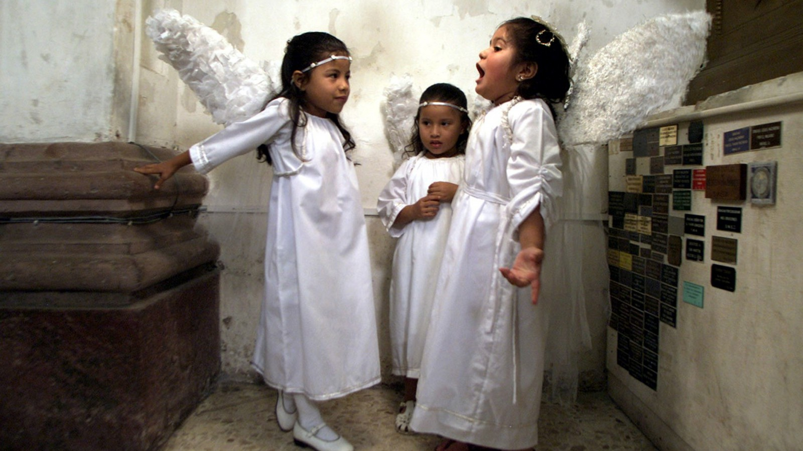 Children dressed as angels chat before participating in a procession in honor of St. Michael the Archangel September 29, 2003 in Tegucigalpa, Honduras. Today also marks Tegucigala's 425 anniversary. REUTERS/Daniel LeClair Pictures of the Year 2003  DNL - RTR3WQG