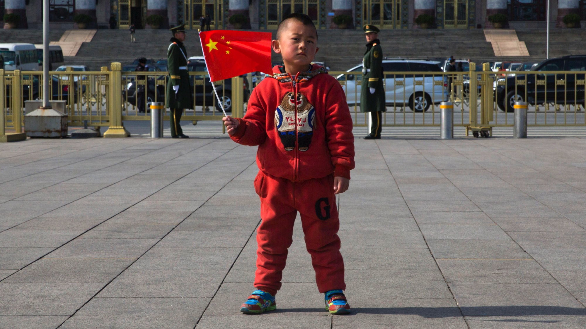 A child holds a Chinese national flag as he poses for photos in front of the Great Hall of the People in Beijing, Wednesday, March 4, 2015. Thousands of delegates from all over the country are in the Chinese capital this week to attend the Chinese People's Political Consultative Conference and the National People's Congress. (AP Photo/Ng Han Guan)