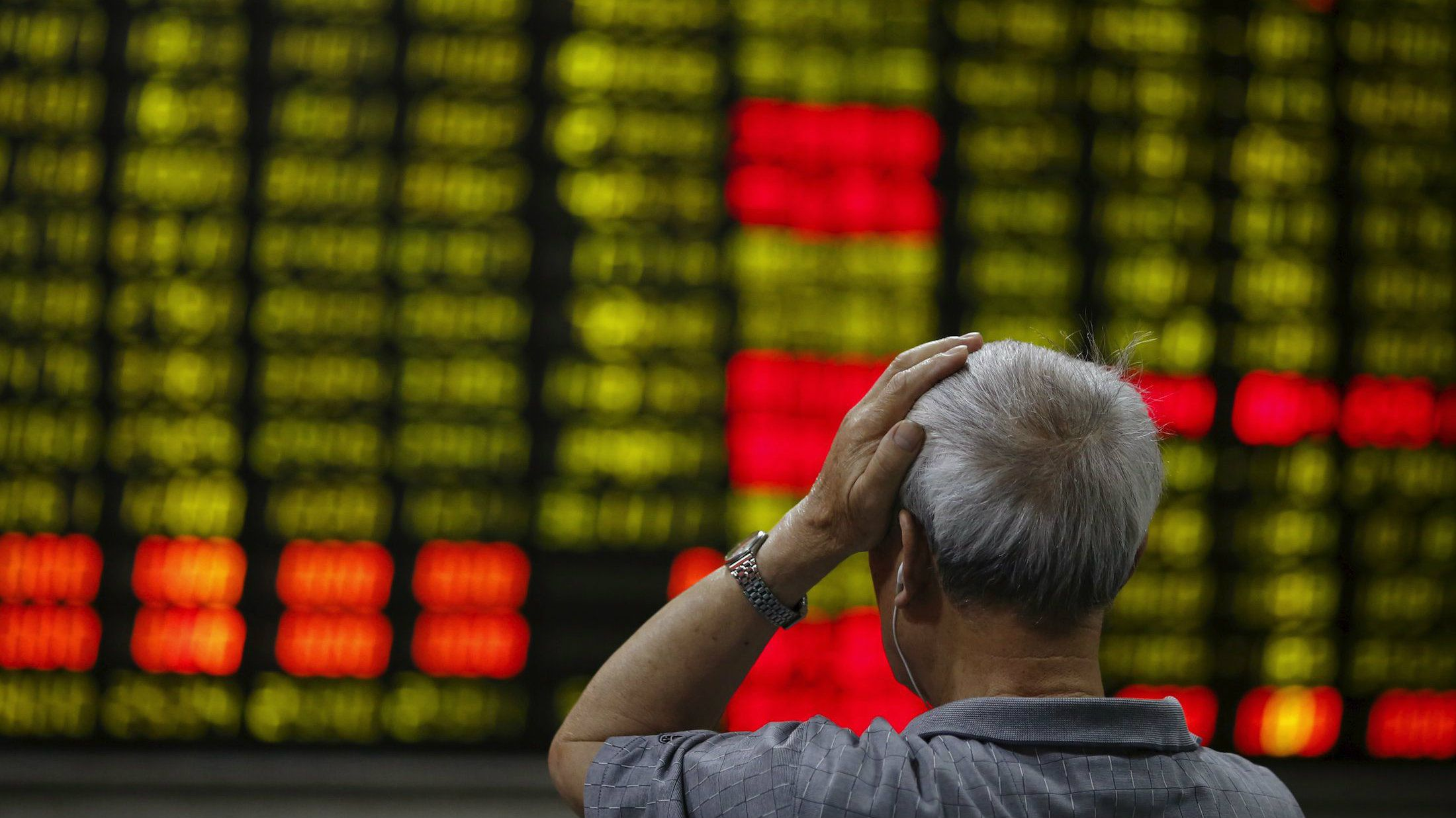 An investor looks at an electronic board showing stock information at a brokerage house in Shanghai.