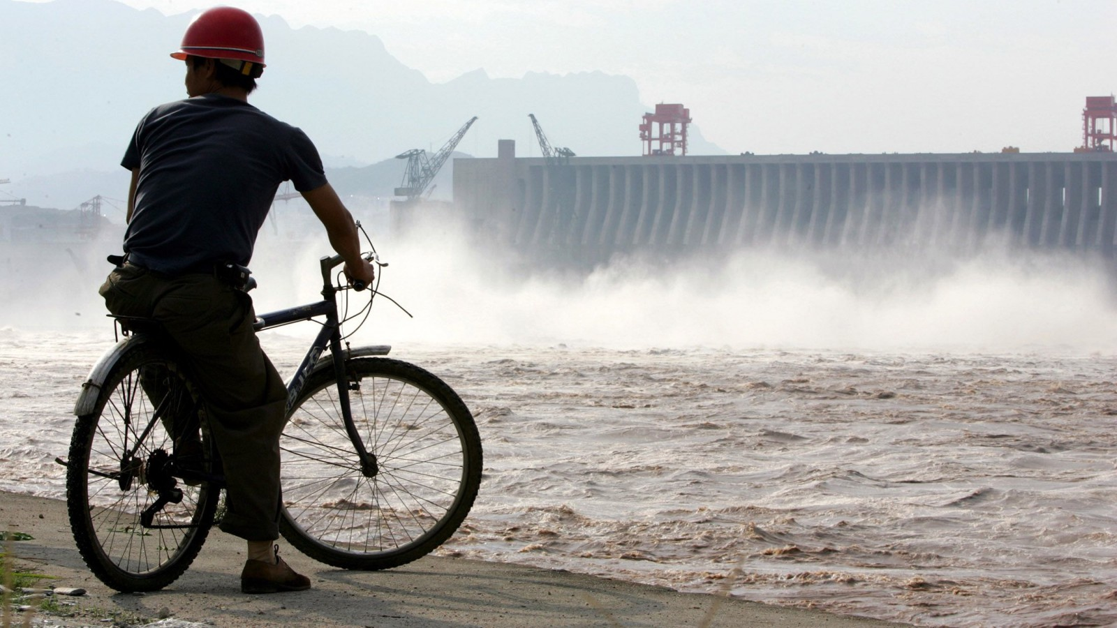 A Chinese worker looks at water gushing from open sluice gates at the Three Gorges dam.