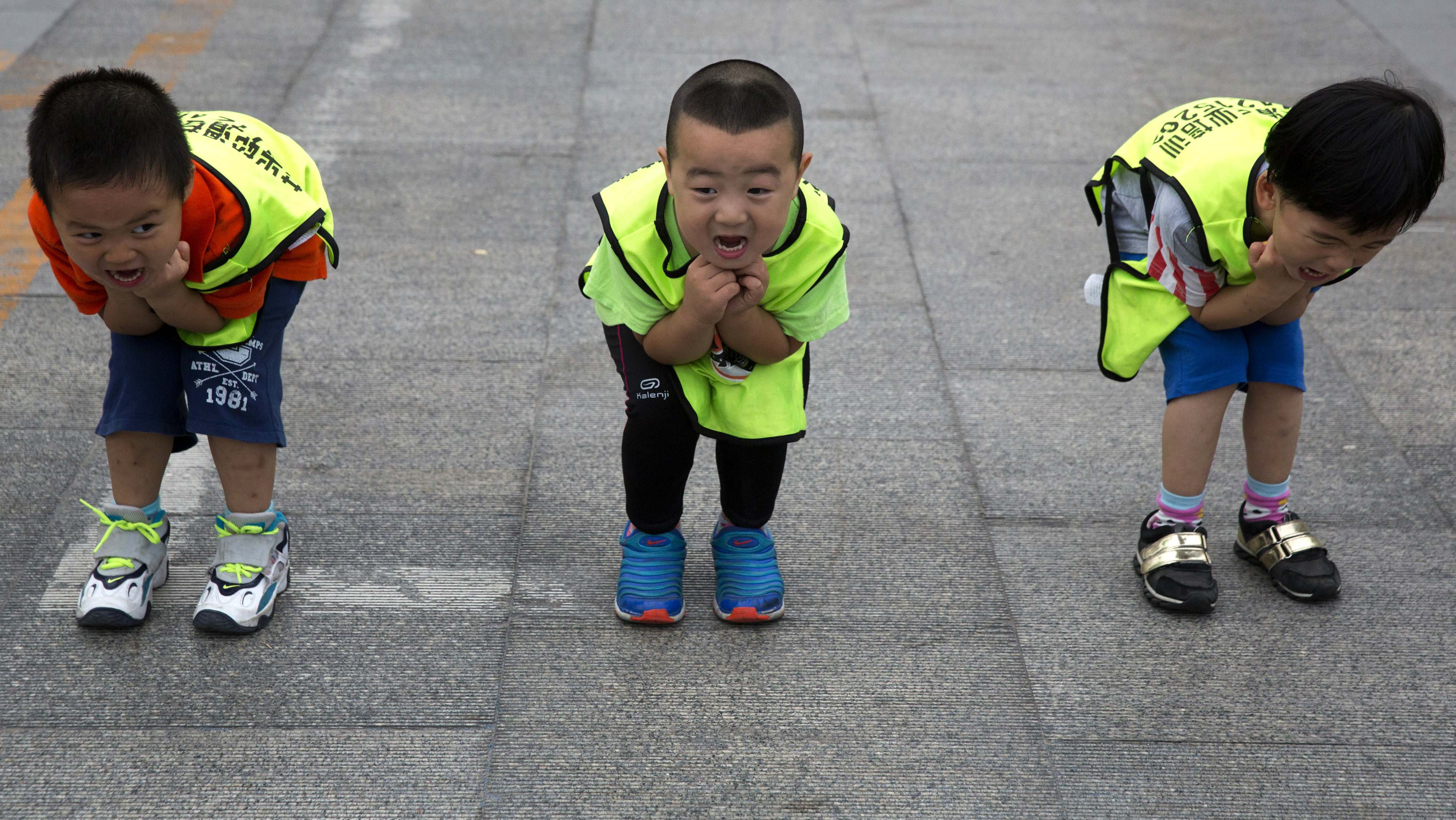 Children practice their postures during a roller blading class outside a park in Beijing, China, Wednesday, June 24, 2015.