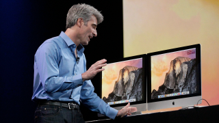 Apple senior vice president of software engineering Craig Federighi speaks over a computer to Beats co-founder Dr. Dre at the Apple Worldwide Developers Conference in San Francisco, Monday, June 2, 2014. (AP Photo/Jeff Chiu)