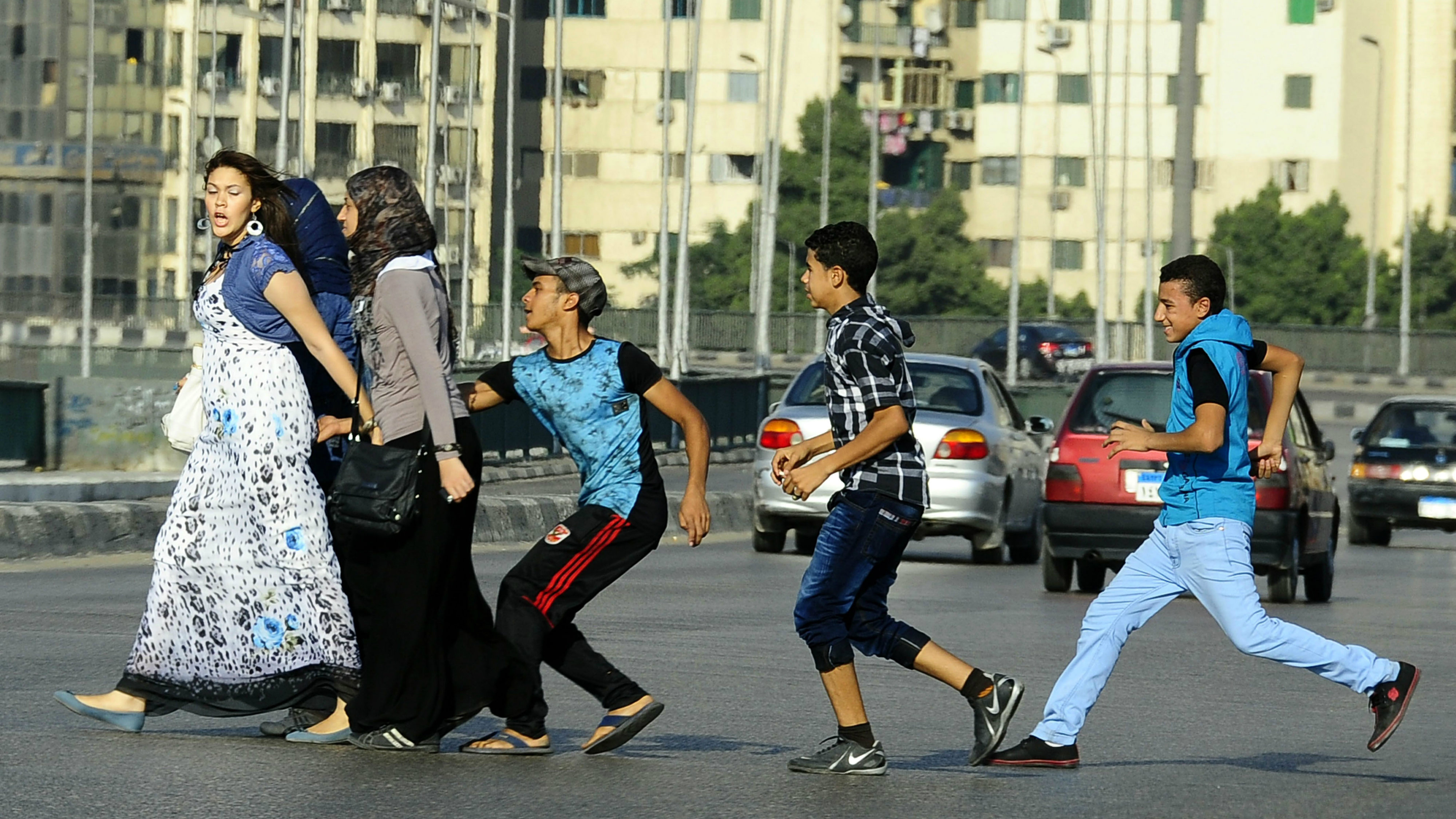 In this Monday, Aug. 20, 2012 file photo, an Egyptian youth, trailed by his friends, gropes a woman crossing the street with her friends in Cairo, Egypt. Abdel-Fattah el-Sissi, Egypt's newly sworn-in president, has apologized in person to a woman who was sexually assaulted by a mob during weekend celebrations marking his inauguration. Several women were assaulted during the Sunday, June 8, 2014 inaugural festivities. (AP Photo/Ahmed Abd El Latif, El Shorouk Newspaper, File)