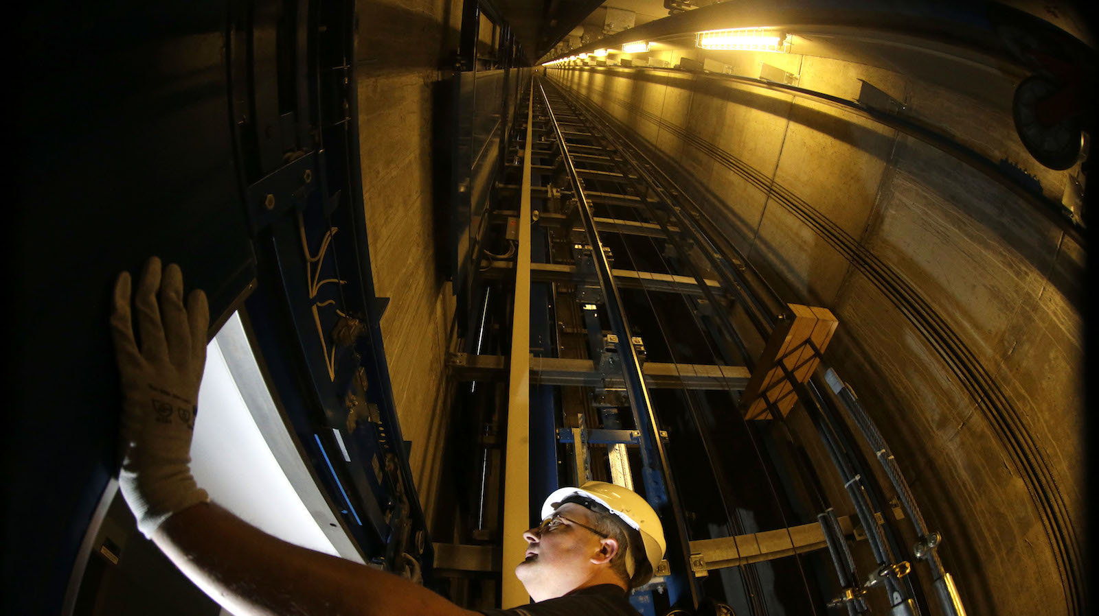 Service engineer of ThyssenKrupp AG inspects door inside elevator shaft in Berlin