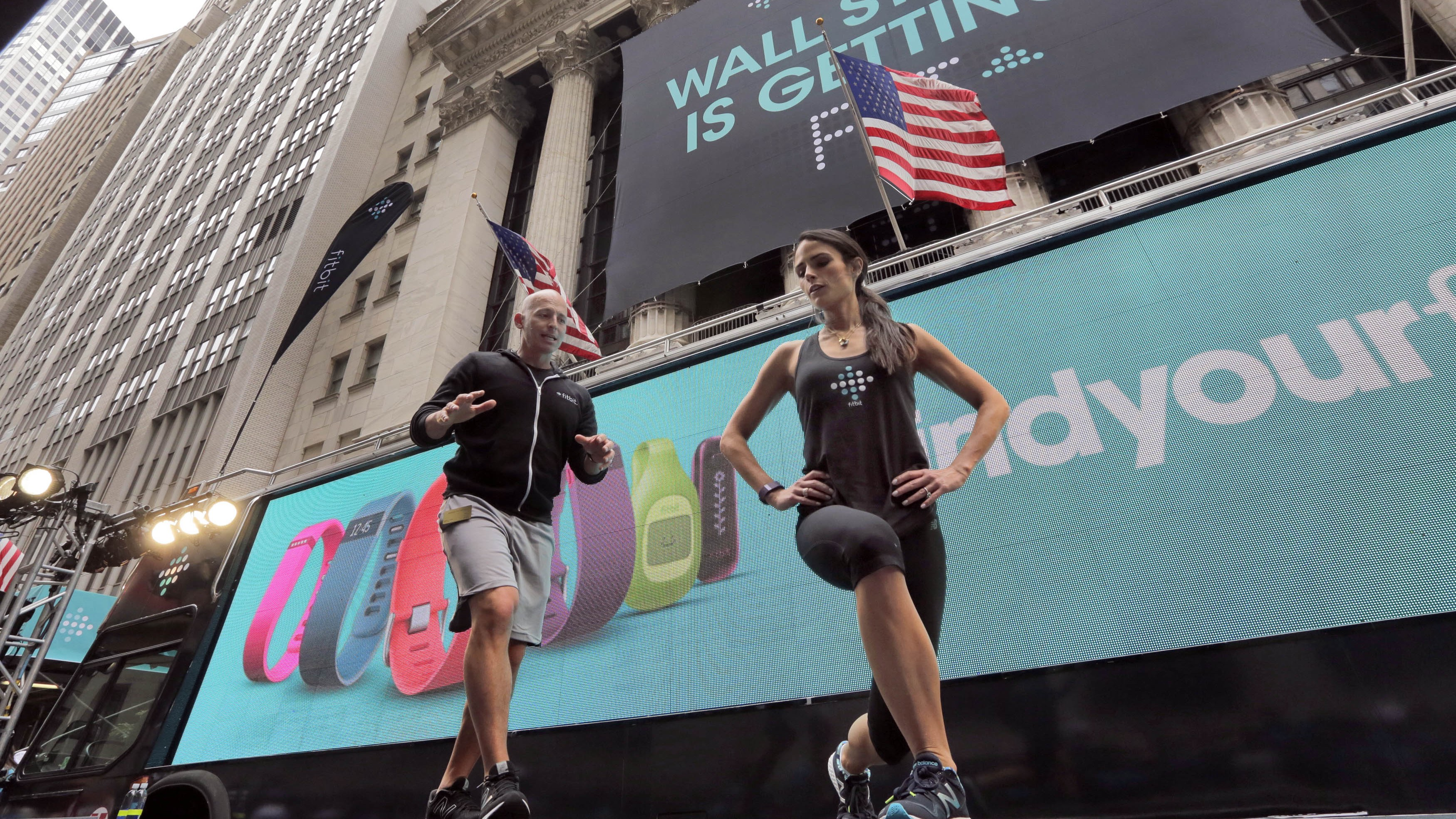 Fitness expert Harley Pasternak and actress Jordana Brewster lead a work out, on behalf of Fitbit, in front of the New York Stock Exchange, Thursday, June 18, 2015. Fitbit flexed some muscle Thursday and its shares rocketed 50 percent higher in the first day of trading for the fitness tracking gear maker. (AP Photo/Richard Drew)