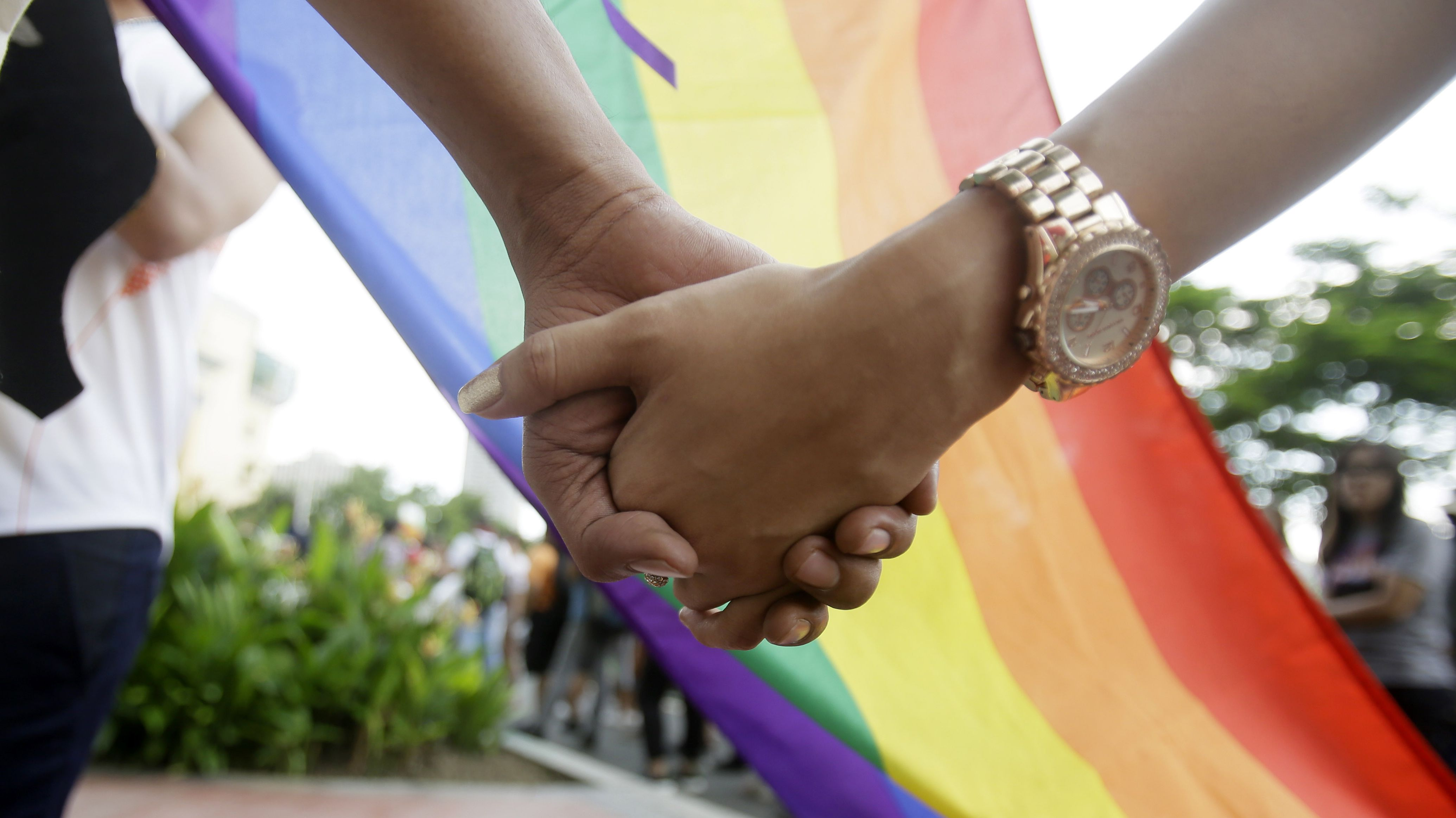 """Filipino LGBTs (Lesbians Gays Bisexual and Transgenders) hold hands as they gather for a Gay Pride rally Saturday, June 27, 2015 in Mania, Philippines to push for LGBT rights and to celebrate the U.S. Supreme Court decision recognizing gay marriages in all U.S. states as a victory for their cause. The rally was scheduled to commemorate the 1969 demonstrations in New York City that started the gay rights movement around the world. Jonas Bagas, executive director of the pro-LGBT rights group TLF Share, said the U.S. court ruling """"will reverberate in other corners of the world."""" (AP Photo/Bullit Marquez)"""