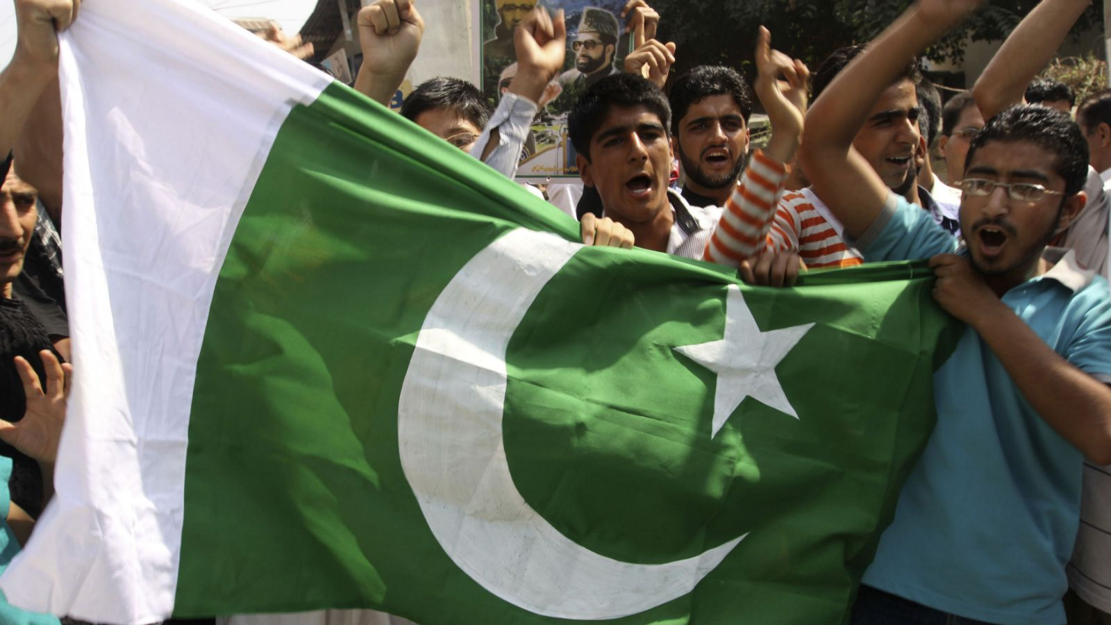 Kashmiri people hold a flag of Pakistan and shout freedom slogans during celebrations marking Pakistani Independence Day in Srinagar, India on Friday, Aug. 14, 2009.