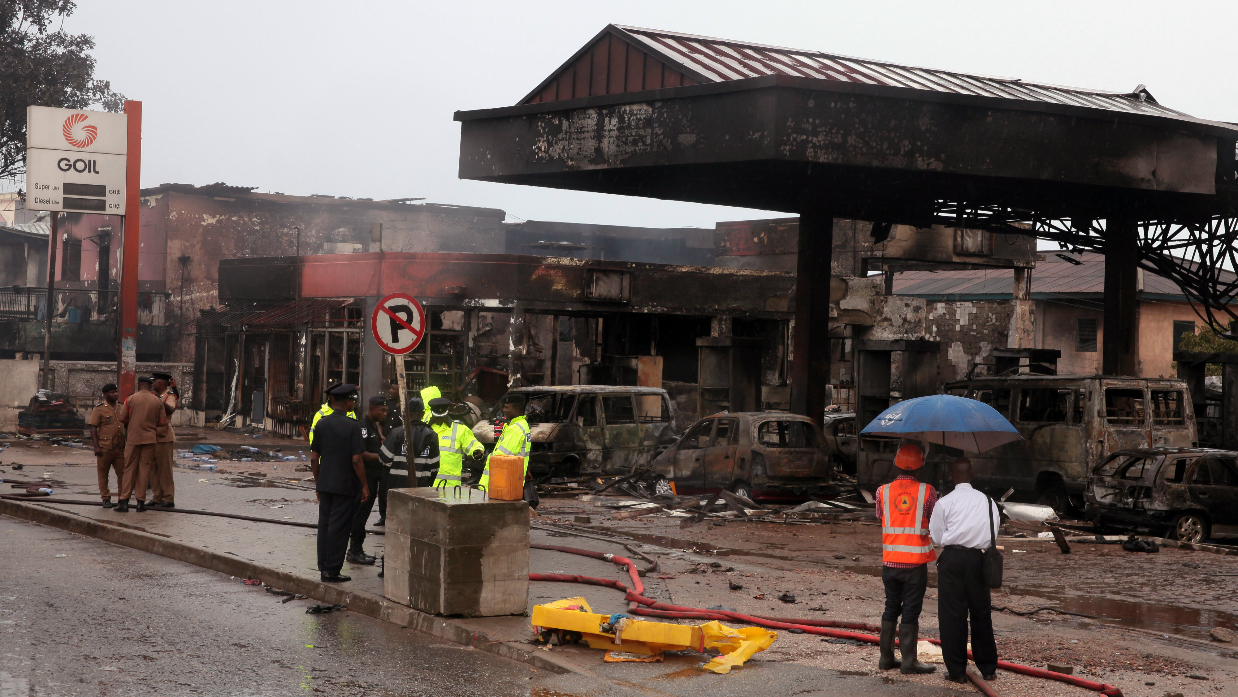 Ghana security personnel stand near the gas station that exploded in Accra, Ghana, Thursday, June 4, 2015. Flooding in Ghana's capital swept stored fuel into a nearby fire, setting off a huge explosion at a gas station that killed scores of people and set alight neighboring buildings, authorities said Thursday. (AP Photo/Christian Thompson)