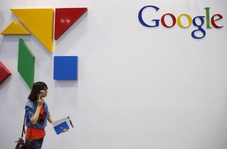 A woman walks past a logo of Google at the Global Mobile Internet Conference in Beijing.