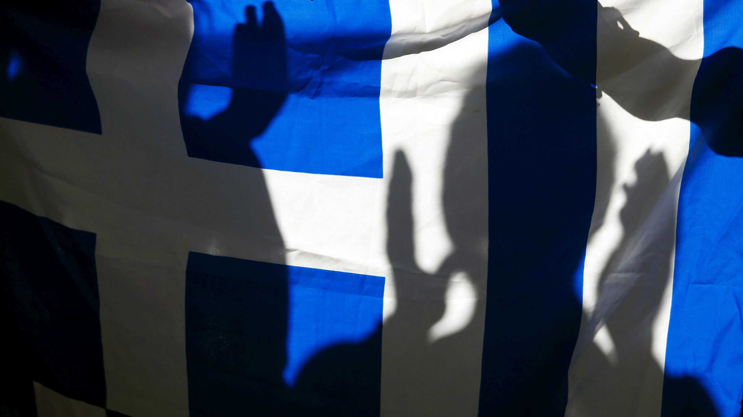 The silhouette of a woman applauding is seen on a Greece flag during a pro-Greece protest in front of the European Union office in Barcelona, Spain, June 29, 2015.