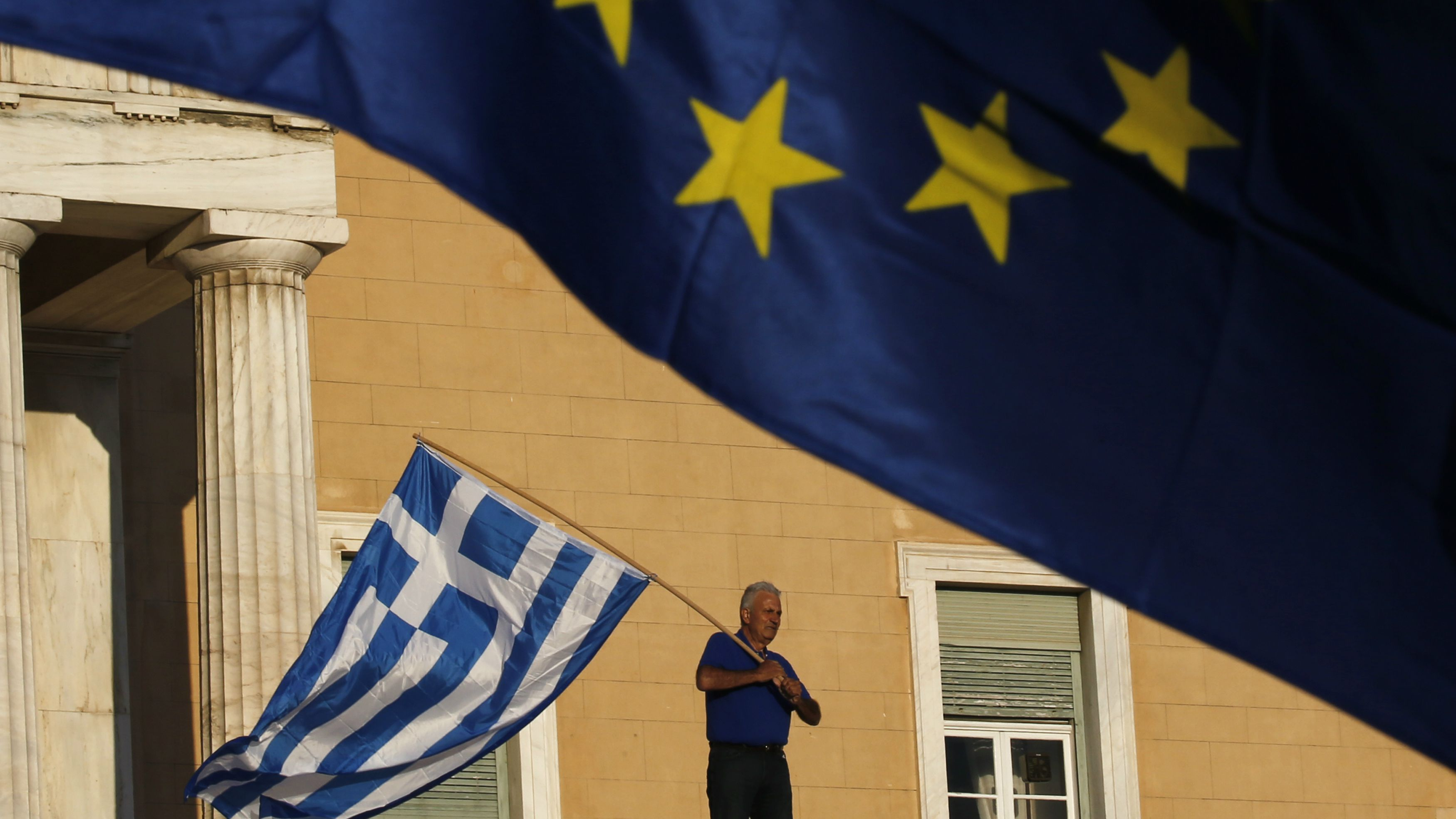 A protester waves a Greek flag at the entrance of the parliament building during a rally calling on the government to clinch a deal with its international creditors and secure Greece's future in the Eurozone, in Athens, Greece, June 22, 2015. Euro zone finance ministers welcomed new Greek proposals for a cash-for-reform deal on Monday but said they required detailed study and it would take several days to determine whether they can lead to an agreement to avert a default. REUTERS/Yannis Behrakis