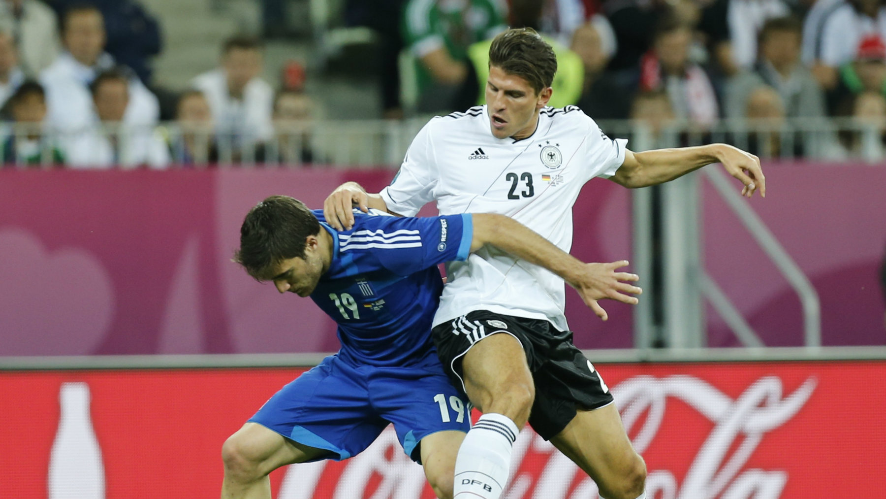 Germany's Mario Gomez (R) challenges Greece's Sokratis Papastathopoulos during their Euro 2012 quarter-final soccer match.