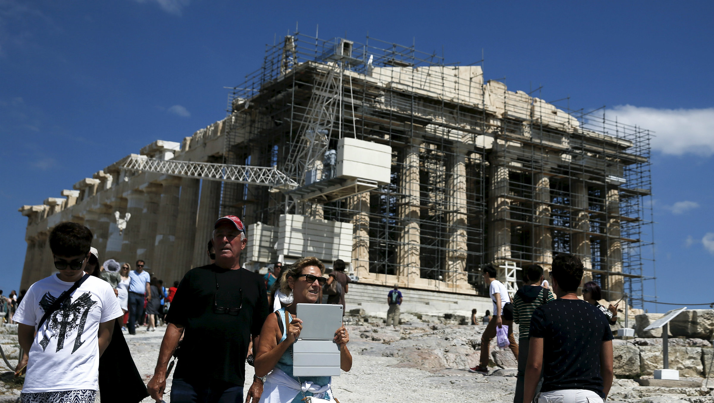Tourists in front of the ancient Parthenon temple atop the Acropolis hill archaeological site.