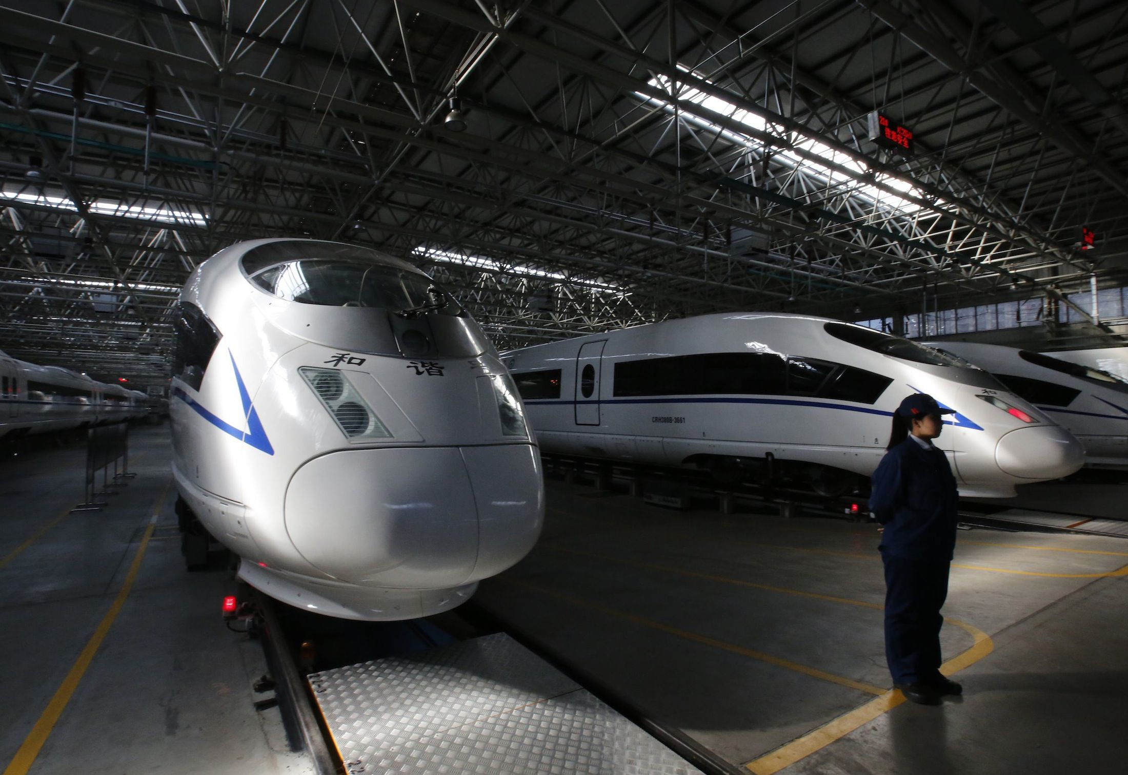 An employee stands next to high speed railway model CRH380B trains at a production line of its parts at China CNR's Tangshan Railway Vehicle's factory in Tangshan, Hebei province