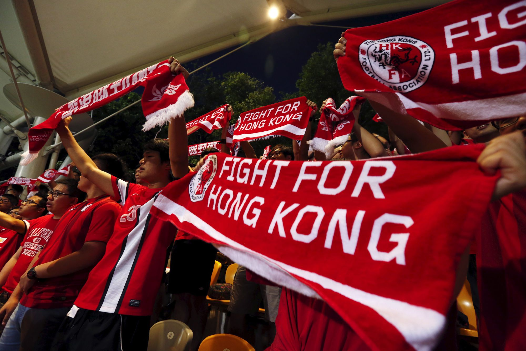 Hong Kong fans sing while holding banners at the World Cup qualifying match between Hong Kong and the Maldives in Hong Kong, China June 16, 2015. Hong Kong's leader warned on Tuesday that violence will not be tolerated, a day after authorities arrested 10 people and seized suspected explosives ahead of a crucial vote on a China-backed electoral reform package this week. Anger has spilled over to football crowds, with supporters of the Hong Kong team loudly booing the Chinese national anthem on Tuesday night at the start of the local World Cup Asian zone qualifying match against the Maldives.