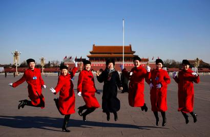 Hotel guides pose for pictures outside the Great Hall of the People at Tiananmen Square ahead of the opening session of the National People's Congress (NPC) in Beijing March 5, 2014.