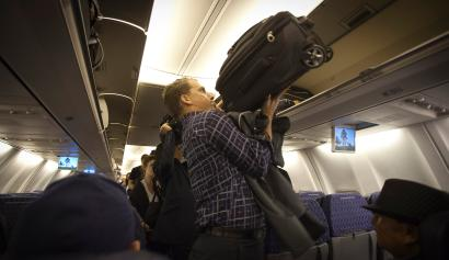 A passenger places his luggage into the overhead bin before an American Airlines flight from Miami to New York December 10, 2013.