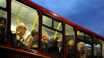Passengers sit on the top deck of a bus in the City of London.
