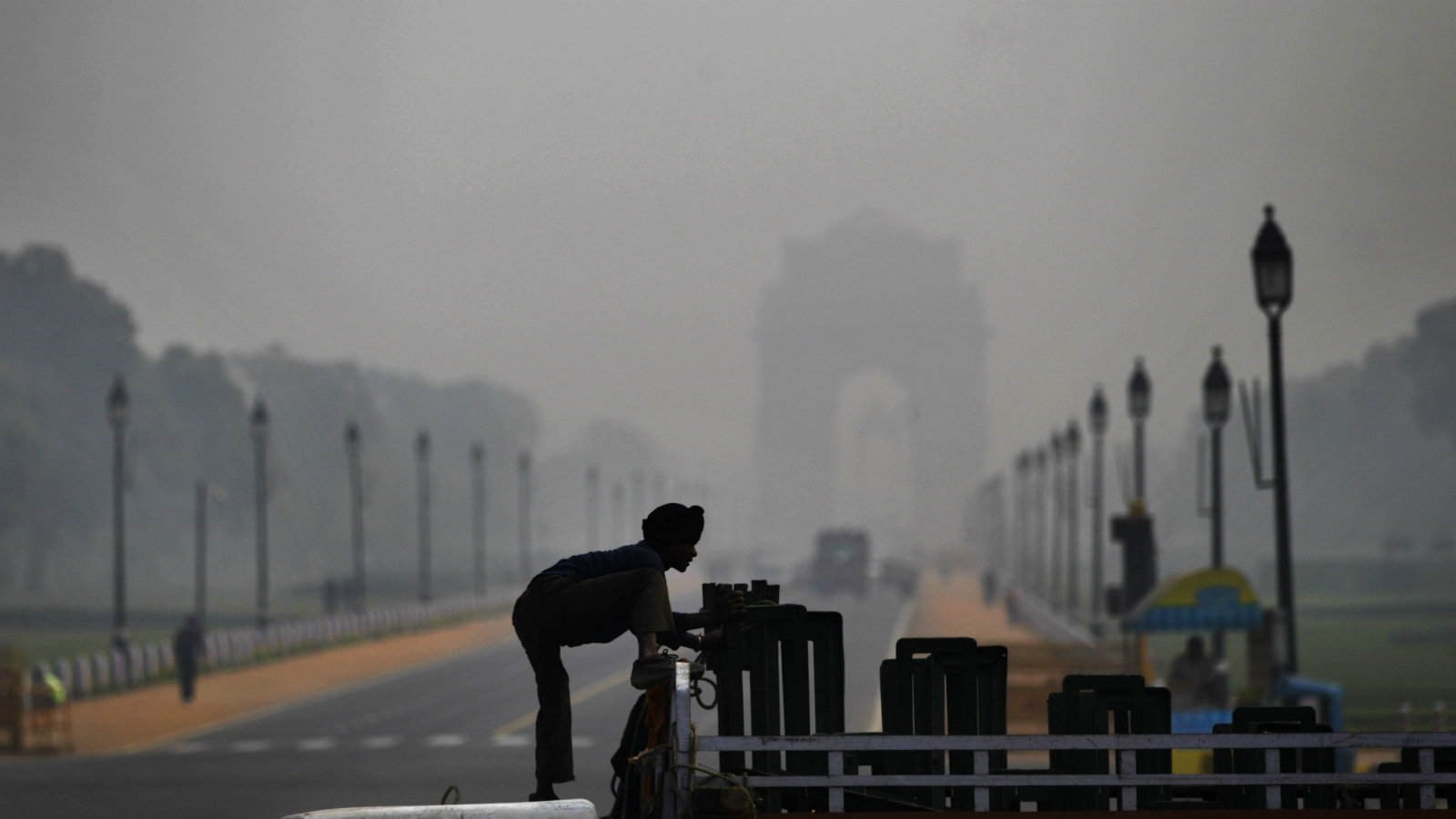 A worker unloads metal frames from a truck in front of the landmark India Gate monument enveloped by a blanket of smog, caused by a mixture of pollution and fog, in New Delhi, India, Thursday, Nov. 8, 2012. (AP Photo/Altaf Qadri)