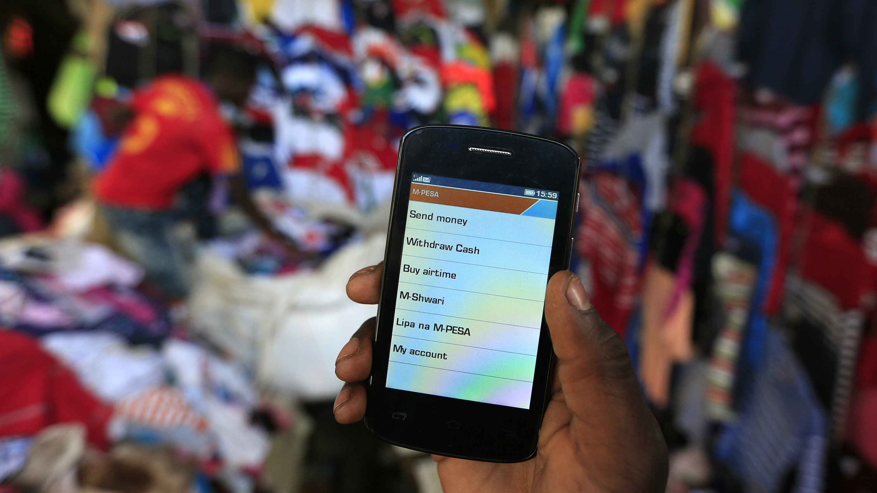 A man holds up his mobile phone showing a M-Pesa mobile money transaction page for the photographer at an open air market in Kibera in Kenya's capital Nairobi.