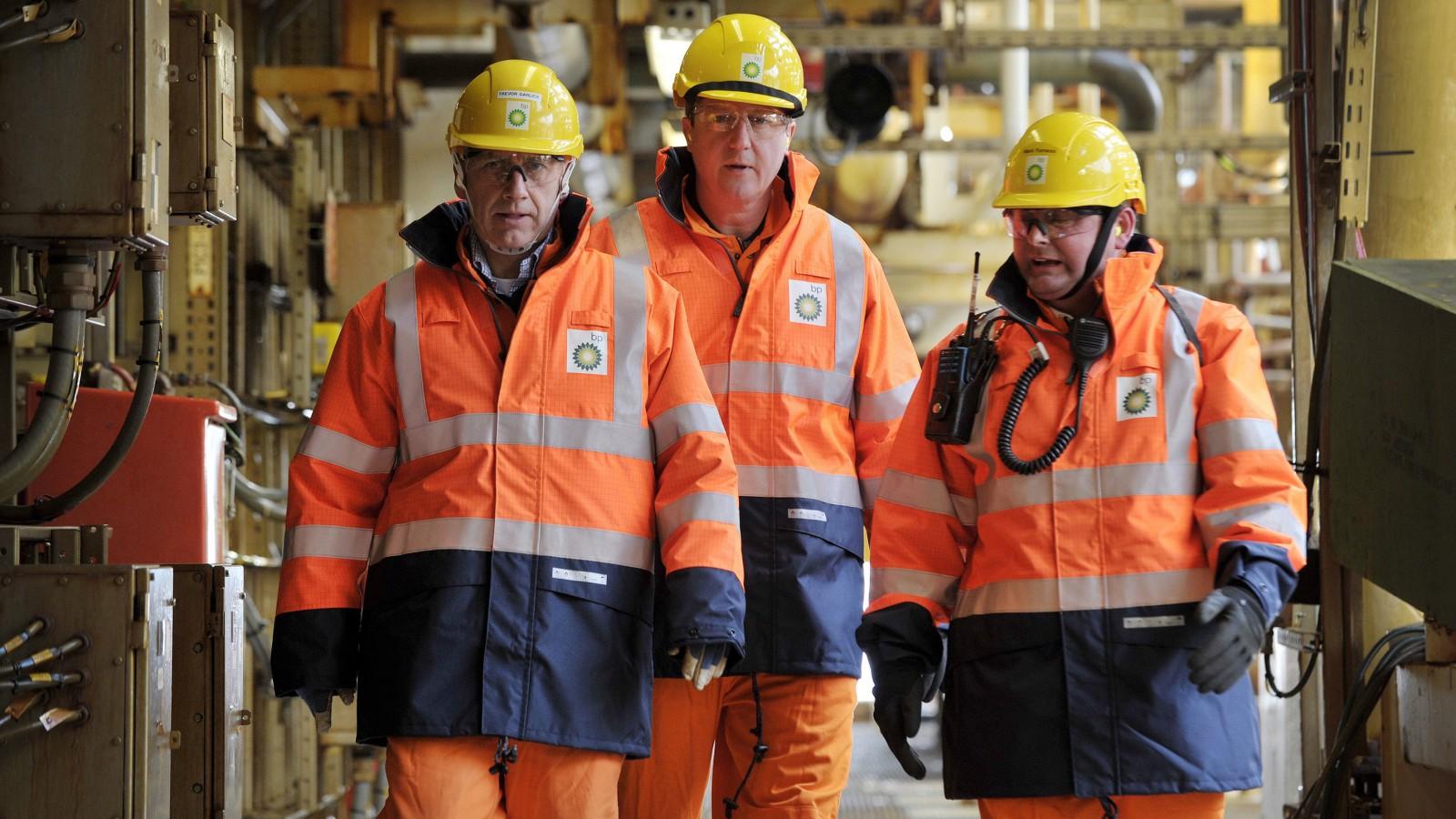Britain's Prime Minister David Cameron (C) walks with BP regional president North Sea Trevor Garlick