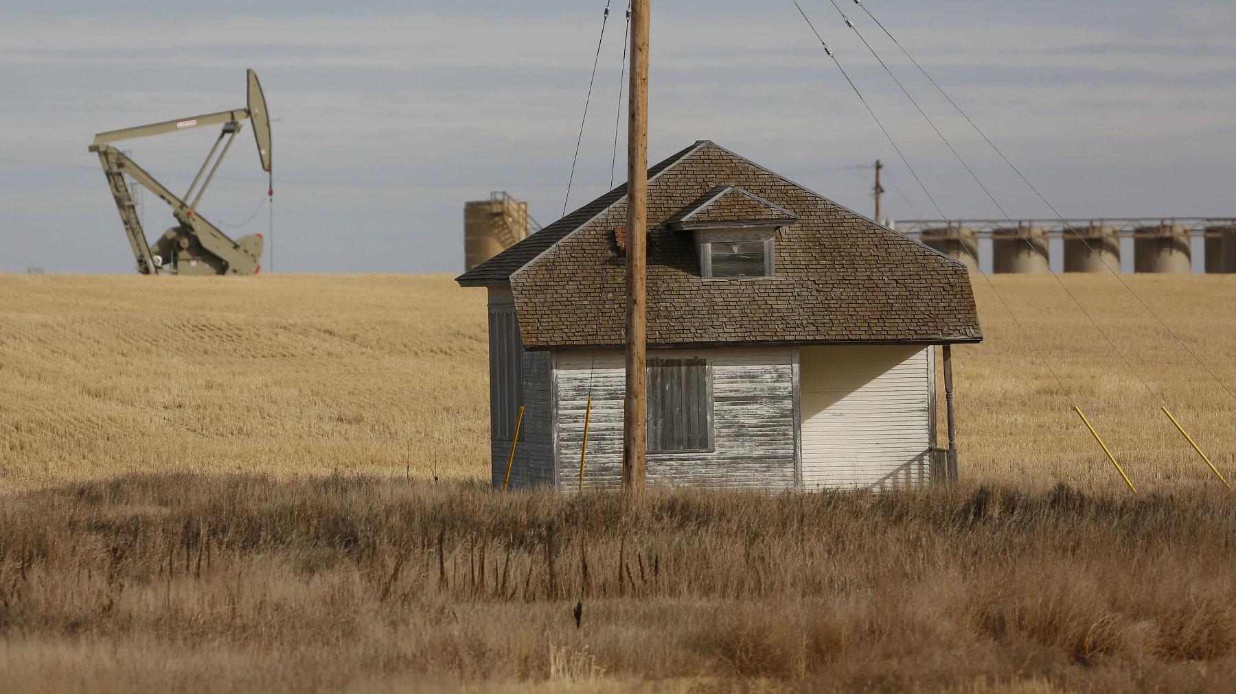 An oil pump jack operates near a vacant farm structure outside Williston, North Dakota.