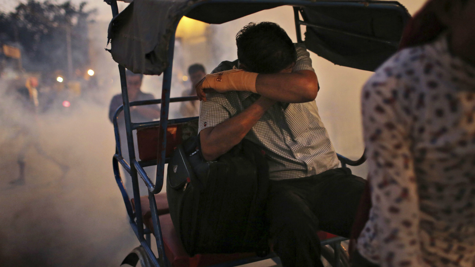 An Indian man covers his face as he rides in the back of a rickshaw as a municipal worker, not seen, fogs for mosquitos on a street in New Delhi, India, Wednesday, Oct. 17, 2012. More than 400 cases of Dengue fever, a mosquito born virus, have been reported in India's capital in a recent outbreak, local media reported. (AP Photo/Kevin Frayer)