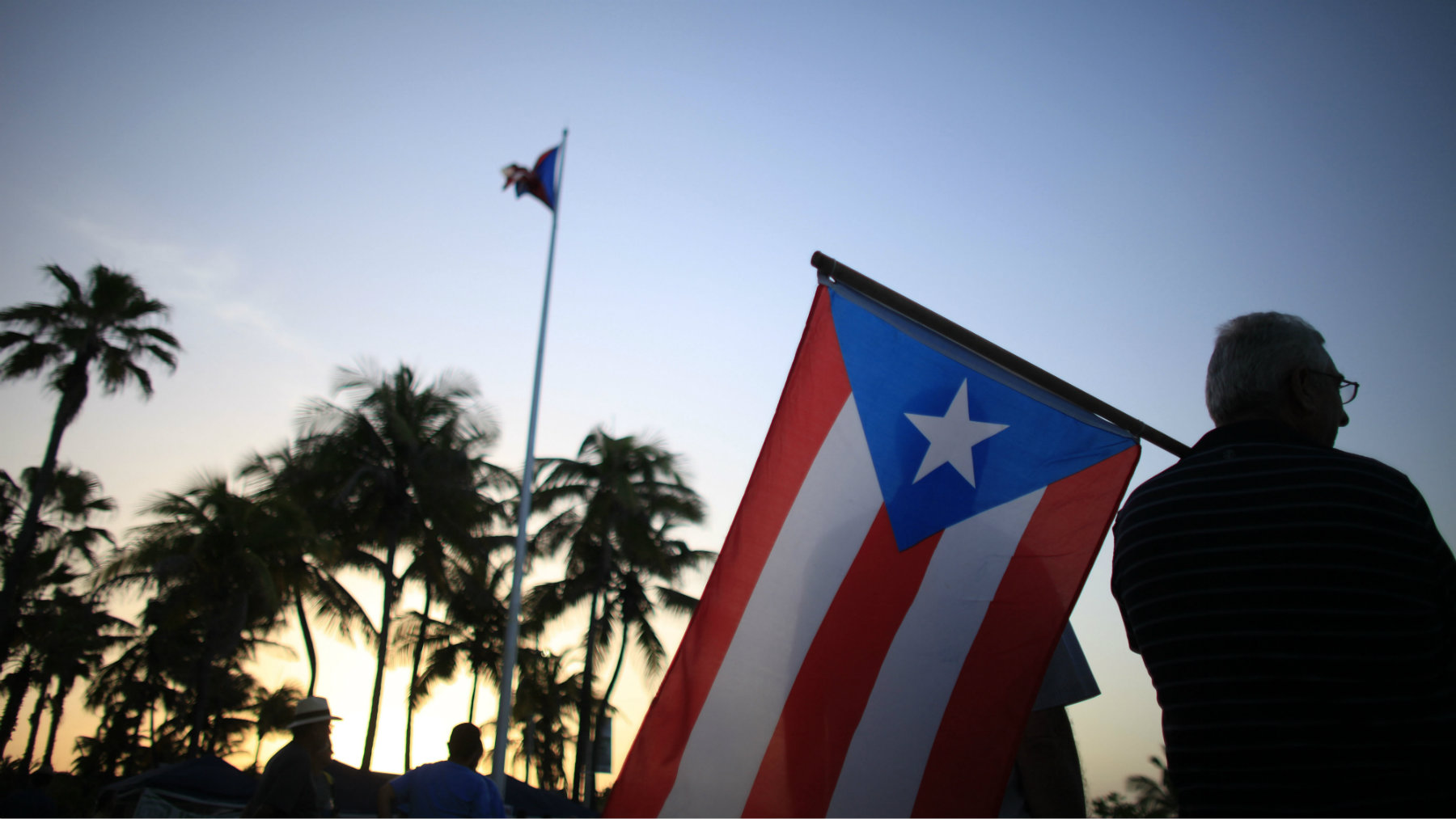 People gather in front of the Puerto Rico's Capitol building to protest against Gov. Alejandro Garcia Padilla's budget proposal for the next fiscal year in San Juan, Thursday, April 30, 2015. Legislators struck down a key part of a plan to overhaul the island's tax system early Thursday, raising concerns about the U.S. territory's economic future and its ability to pay off a heavy public debt. (AP Photo/Ricardo Arduengo)