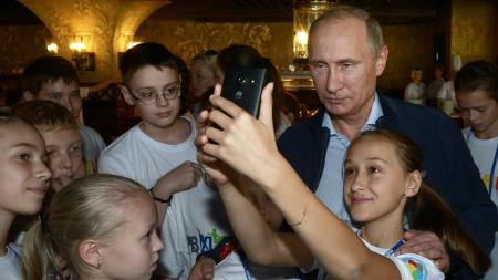 A girl takes a self portrait with Russian President Vladimir Putin as he vists a sports center for children in the Black Sea resort of Sochi, Russia, Saturday, Oct. 11, 2014.