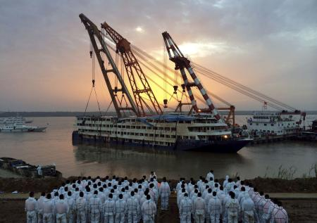 Rescue workers stand on the river bank as the capsized cruise ship Eastern Star is pulled out of the Yangtze against sunset, in Jianli, Hubei province, China, June 5, 2015. Only 14 survivors, one of them the captain, have been found after the ship carrying 456 overturned in a freak tornado on Monday night