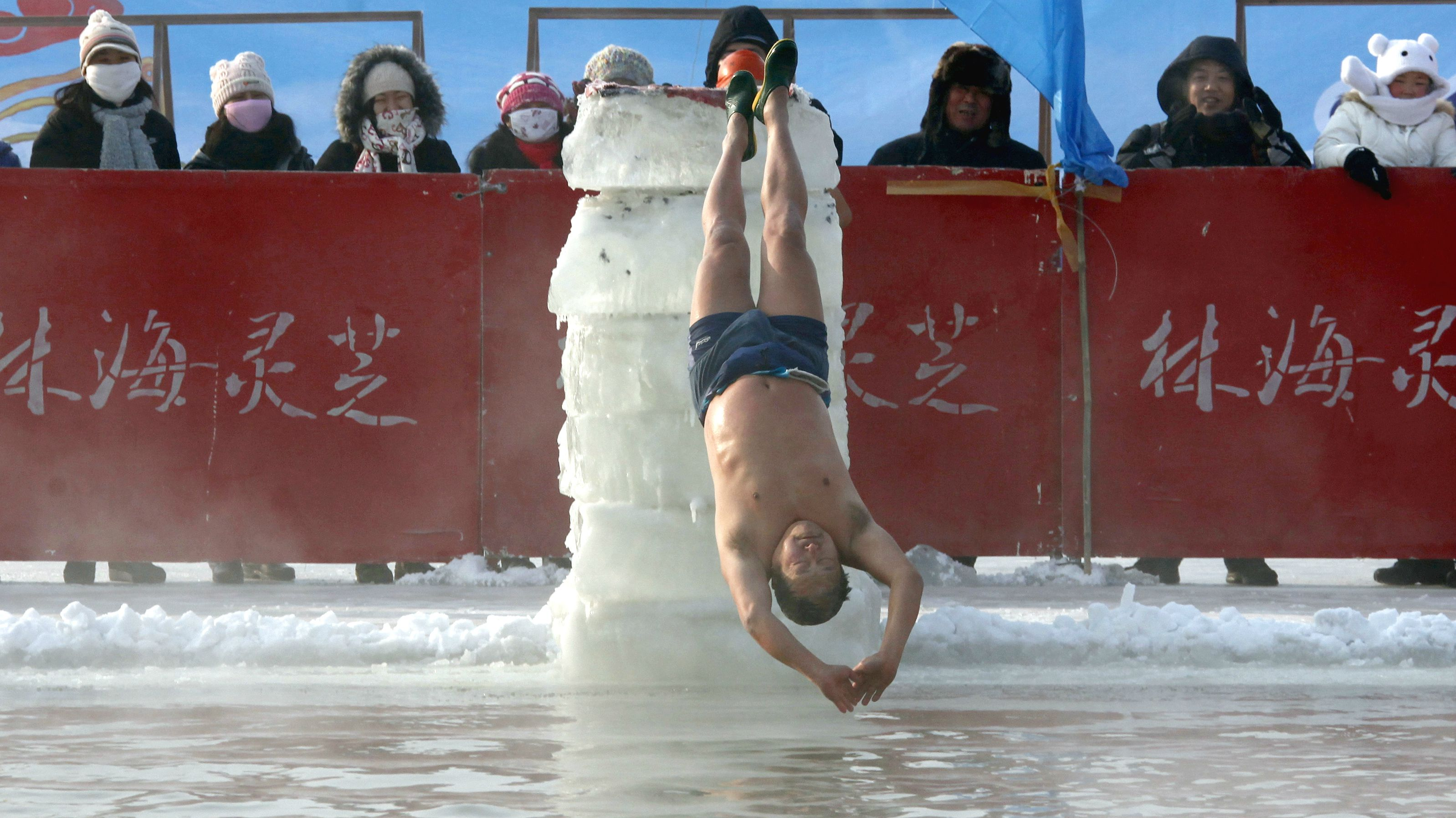 DATE IMPORTED:January 04, 2011A man dives backwards off a ice block into a pool carved out of the thick ice covering the Songhua River in the northern city of Harbin, Heilongjiang province January 4, 2011. The swimming display is part of the Harbin International Ice and Snow Festival which will be officially launched on January 5. REUTERS/David Gray