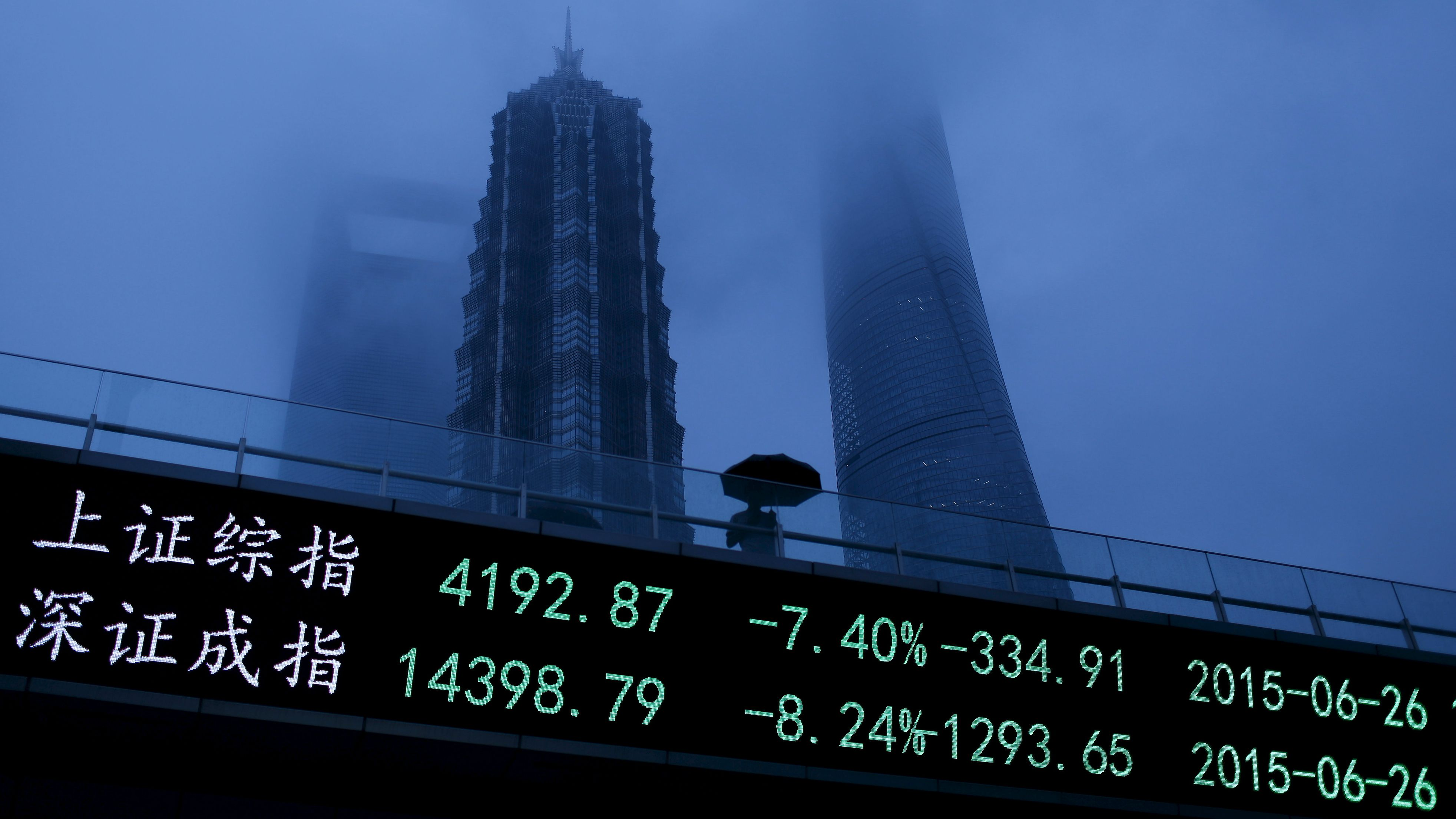 A man walks past an electronic board showing the benchmark Shanghai and Shenzhen stock indices, on a pedestrian overpass at the Pudong financial district in Shanghai, China, June 26, 2015. Chinese stocks plunged over 7 percent on Friday, with one key index recording its biggest fall since 2008, hit by tight liquidity conditions ahead of the quarter-end and uncertainty over the central bank's easing policy. REUTERS/Aly Song