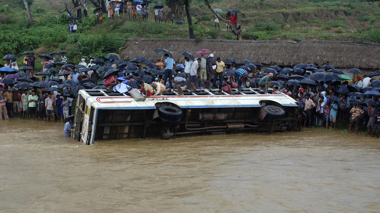 Onlookers stand next to an overturned passenger bus that was washed away by flash floods in Bankura district of the eastern Indian state of West Bengal September 6, 2012. A bus carrying about 50 passengers was washed away by flash floods with 45 passengers rescued while the rest are still missing, local media reported.