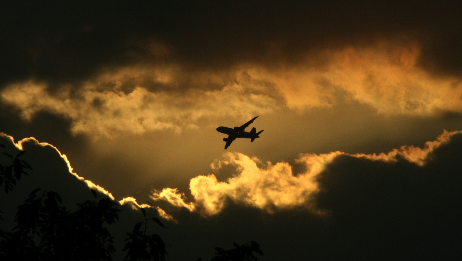 An aircraft flies against the backdrop of pre-monsoon clouds in New Delhi July 6, 2006. Monsoon rains in India kill hundreds of people, damage homes and destroy crops almost every year.