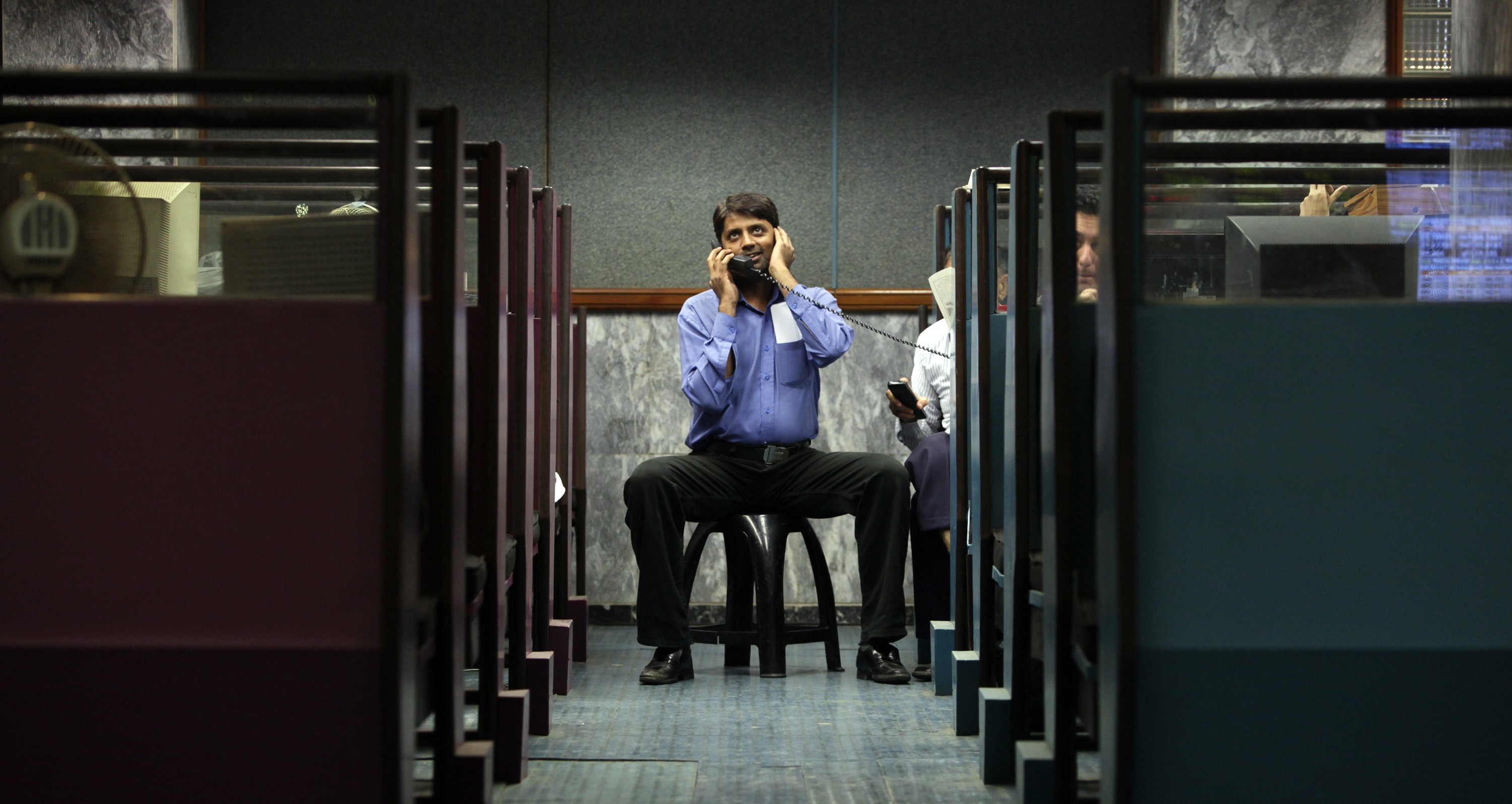 A man uses a phone between booths while monitoring share prices during a trading session at the Karachi Stock Exchange August 10, 2011.