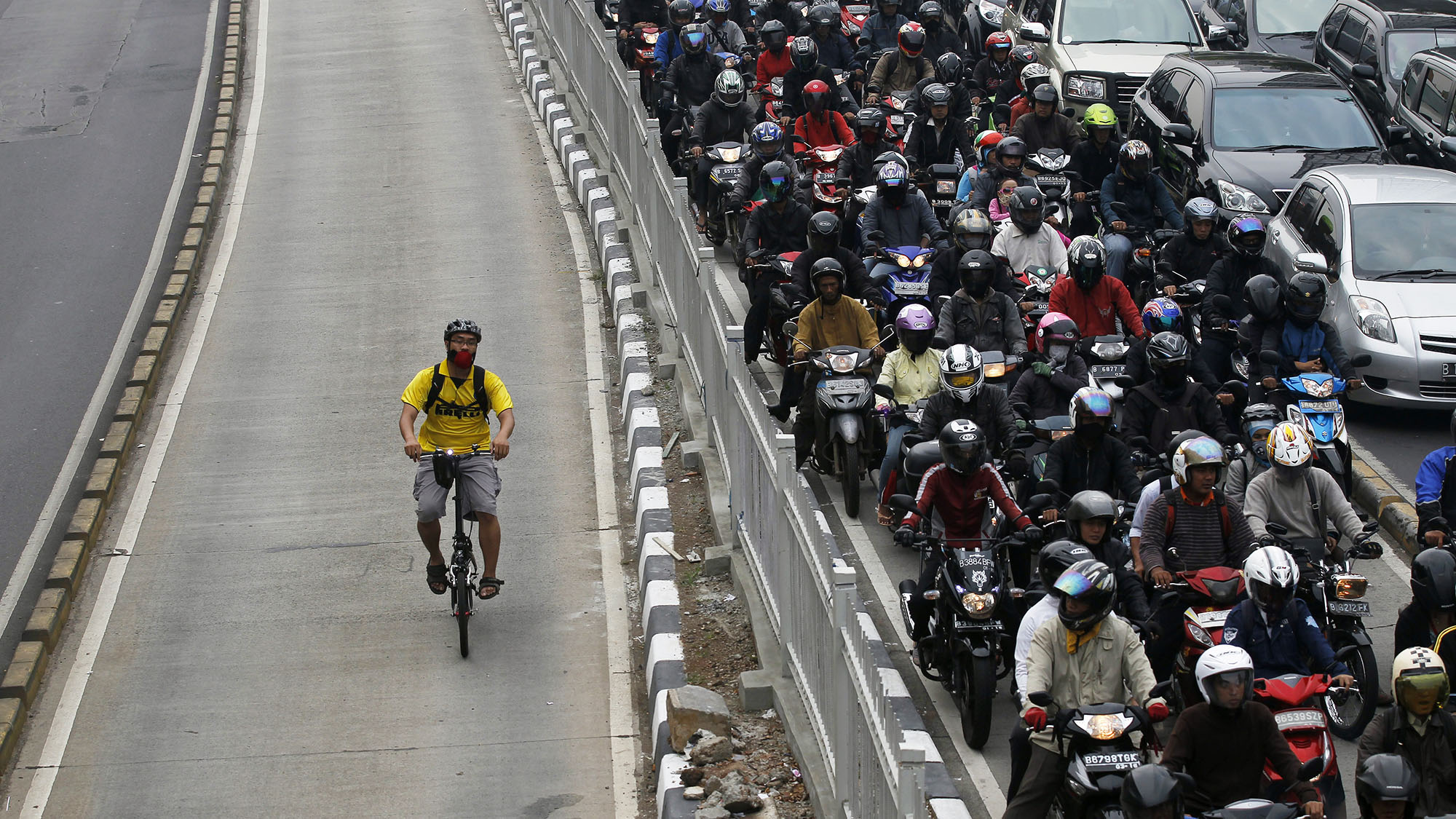 A man rides a bicycle in a bus lane next to a morning rush hour traffic jam in Jakarta November 10, 2011. Indonesia's central bank said on Thursday it saw economic growth in 2012 could slow to below 6.5 percent, as it cut its benchmark overnight interest rate by a surprise 50 basis points to a record low 6 percent to ward off the effect of a slowdown in Europe and China.