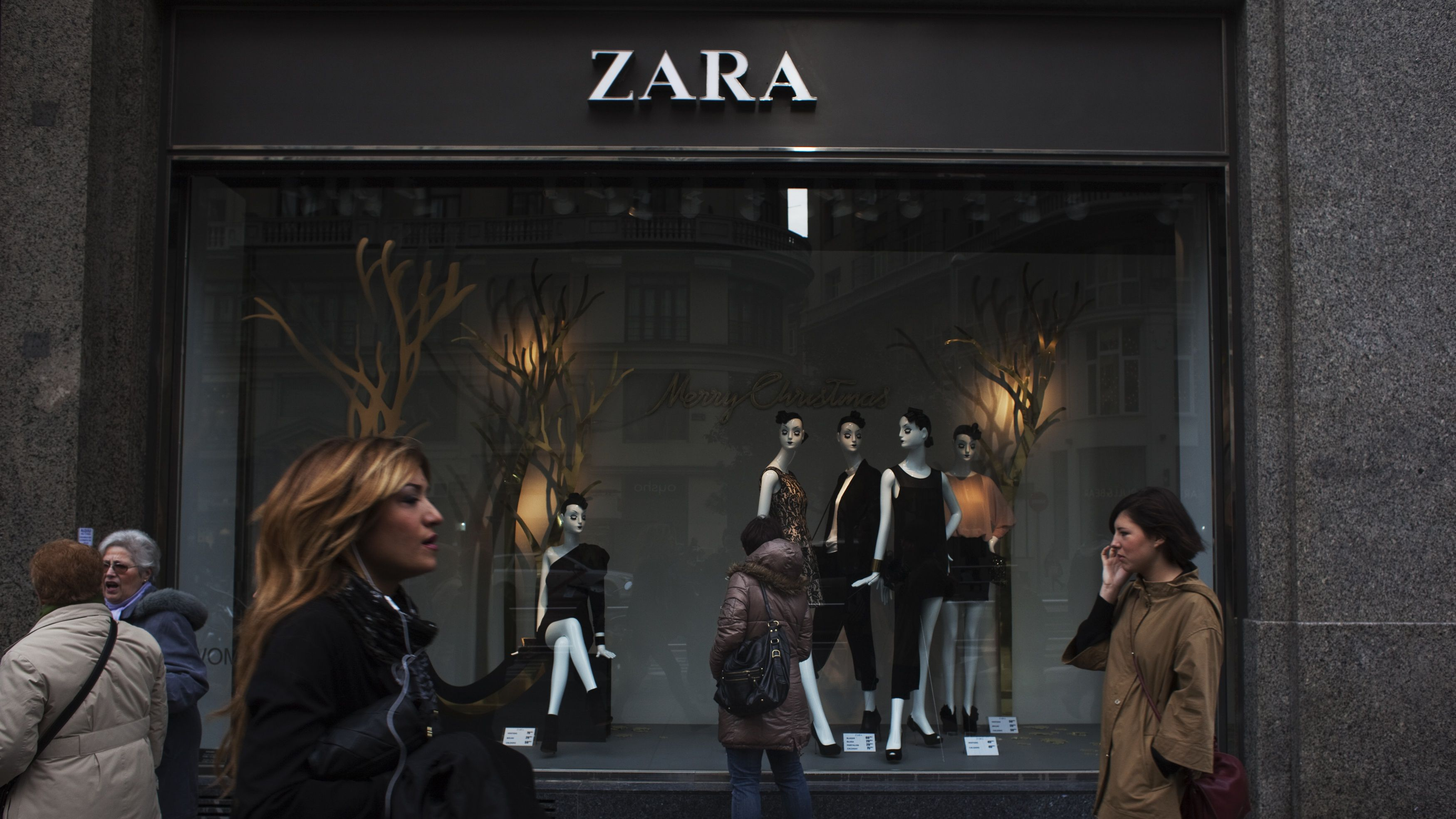 People walk by one of Zara's stores in central Madrid December 14, 2011. Sales growth at Spain's Inditex, the world's largest clothing retailer and owner of the popular Zara label, eased in the third quarter as the euro zone debt crisis rattled shoppers and unseasonably good autumn weather altered spending patterns. But the company, founded by Spain's richest man Amancio Ortega, still cheered the market with evidence it remains capable of outperforming rivals. The group reported a surprise 100 basis point increase in its profit margin and said sales growth in the fourth quarter had recovered.