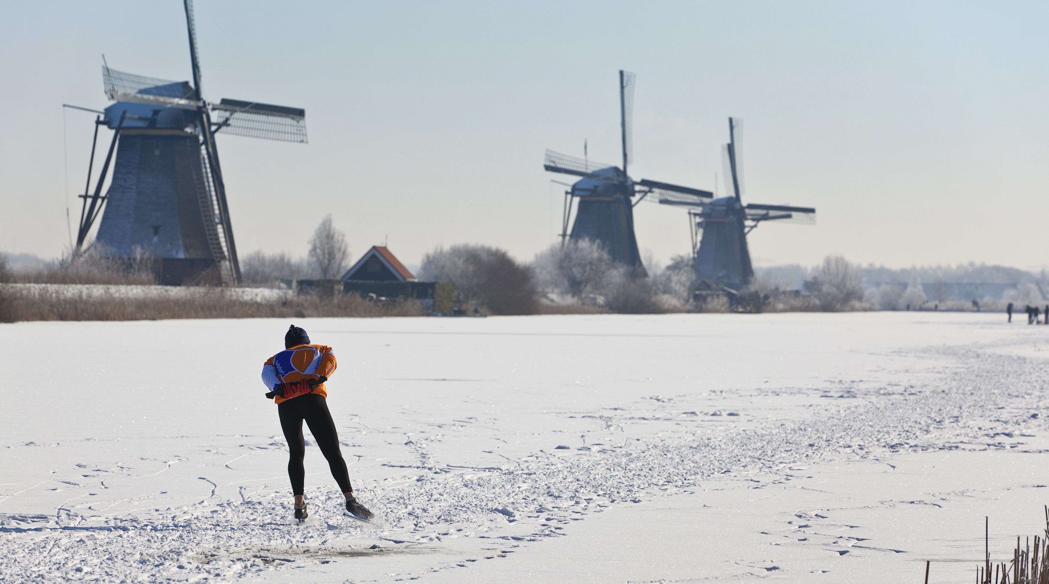 A lone skater skates past three windmills as he enjoys the first time he can skate on natural ice in Kinderdijk, near Rotterdam February 4, 2012. The 19 windmills near Kinderdijk are on the UNESCO world heritage list. REUTERS/Michael Kooren (NETHERLANDS - Tags: SOCIETY ENVIRONMENT) - RTR2XBDE