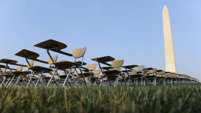 """An art installation of 857 empty school desks stands at the National Mall, near the Washington Monument, in Washington June 20, 2012. Each of the desks represents a U.S. student who drops out every hour of every school day, according to the College Board which set up the installation. A team of local college students, supporting the """"Don't Forget Ed"""" national movement, collected signatures on site for a petition to be sent to U.S. presidential candidates asking them to prioritize education in the presidential campaign."""